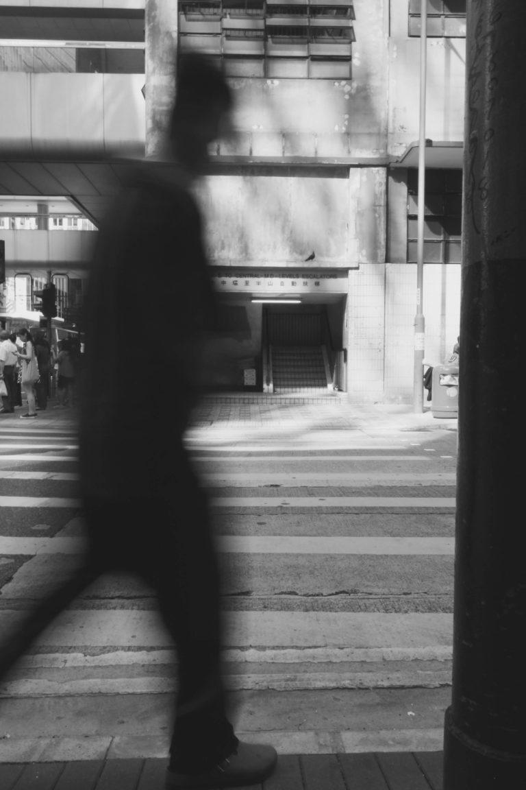 hong kong walking man in front of train station in black and white